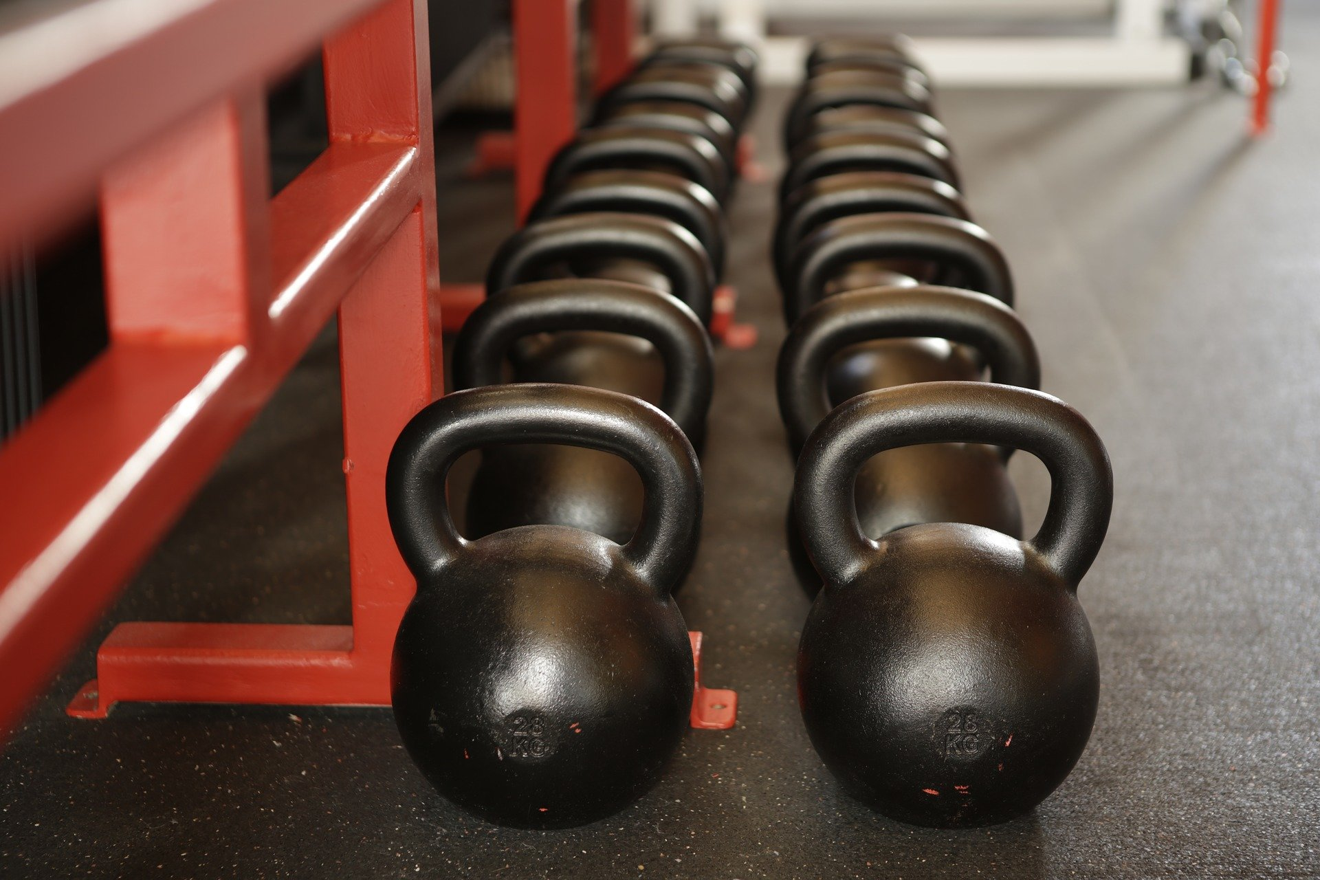 black kettlebells on the floor in a gym